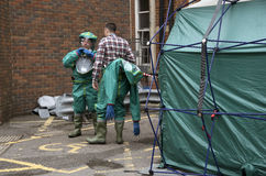 Decontamination tent and men removing their protective clothing Stock Photos