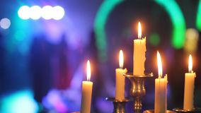 Decor candles at table in the restaurant. Defocused people dancing background of burning candles. Decor candles at table in the restaurant. Defocused people stock video