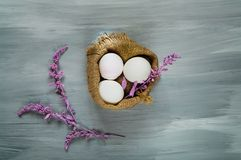 Decor for Easter holidays, a willow branch and decorative colored eggs in burlap on a  blue background,. Decor for Easter holidays, a willow branch and Stock Photos