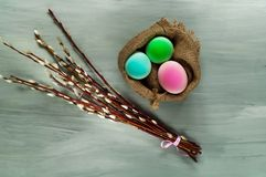 Decor for Easter holidays, a willow branch and decorative colored eggs in burlap on a concrete blue background, top view. Decor for Easter holidays, a willow Stock Photo