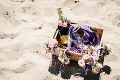 Decorated box with champagne, wine and glass on the beach. Decor of flowers on the sand on the beach. Decorated box with champagne, wine and glass. Place for stock images