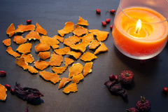 Decor heart  for Valentines Day. Greeting decor for Valentines Day: Heart made from dry orange peel, candle and dry berries Stock Photography