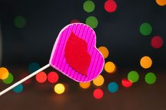 Decor for the holiday. Heart of hand made cardboard on a dark background with bright lights Stock Photography