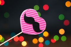 Decor for the holiday. Heart of hand made cardboard on a dark background with bright lights Stock Image