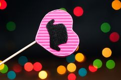 Decor for the holiday. Heart of hand made cardboard on a dark background with bright lights Stock Images