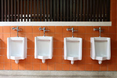 Decor interior of white urinals in men bathroom Stock Photos