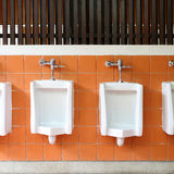 Decor interior of white urinals in men bathroom Stock Images