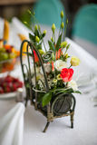 Decor table with a basket of flowers Royalty Free Stock Photography