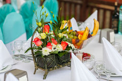 Decor table with a basket of flowers Stock Photos