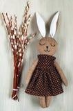 Decor voor Pasen-vakantie, een wilgentak en een konijn van met de hand gemaakte textiel op een houten achtergrond, een hoogste me Stock Foto