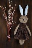 Decor voor Pasen-vakantie, een wilgentak en een konijn van met de hand gemaakte textiel op een houten donkere achtergrond, een ho Royalty-vrije Stock Afbeeldingen