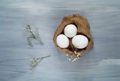 Decor voor Pasen-vakantie, eieren op een textuur van jute op een houten lichte achtergrond, hoogste mening, vrije ruimte voor tek Royalty-vrije Stock Foto's