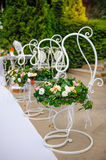 Decor of the wedding flowers in baskets hanging on a metal stand Royalty Free Stock Photo