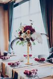 Decor of a wedding restaurant in maroon color with flowers. And details stock images