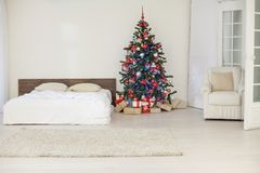 Decor white bedroom with Christmas tree Christmas gifts. 1 Stock Photography