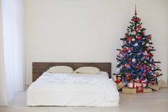 Decor white bedroom with Christmas tree Christmas gifts. 1 Stock Photo