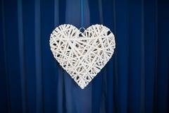 Decor wicker heart on a blue background Stock Photos