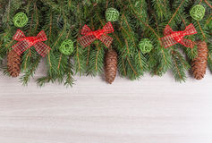 Decor winter holidays fir branches with cones with green clouds of twigs and red bow Royalty Free Stock Image
