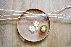 Decor of zen meditation, mindfulness or pampering massage, above view. Feng shui round wooden tray, candle, twigs and white beautiful flowers for decor of zen Royalty Free Stock Photos