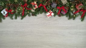 A decoração aérea dando laços cobre o quadro no fundo de madeira claro com cones do pinho, presentes, fitas vermelhas do ouro, pi filme