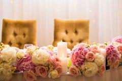 A decoração, as flores e as velas do casamento decoraram as cadeiras de tabela Imagens de Stock Royalty Free