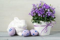 Decoração bonita de easter com flores da campânula, ovos da páscoa e coelho cerâmico, no fundo de madeira branco Fotografia de Stock Royalty Free
