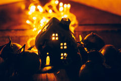 A decoração bonita do Natal com tangerinas e uma casa do brinquedo na noite iluminam festões Do citrino vida ainda Fotografia de Stock Royalty Free