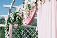 Decoração bonita para a cerimônia de casamento do verão fora Arco do casamento feito do pano claro e das flores brancas e cor-de- Foto de Stock