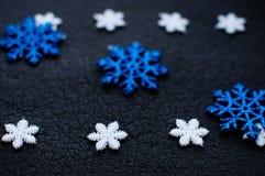 Decoração branca e azul dos flocos de neve do Natal no fundo textured preto Fotografia de Stock Royalty Free