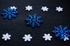 Decoração branca e azul dos flocos de neve do Natal no fundo textured preto Imagens de Stock