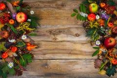 A decoração da ação de graças com abóbora, maçãs e verde sae na madeira Fotografia de Stock Royalty Free