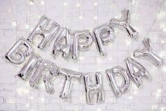 Decoração da festa de anos - as letras do feliz aniversario arejam balões sobre a parede de tijolo com luzes
