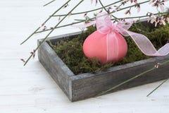 Decoração da Páscoa, único ovo cor-de-rosa em uma caixa de madeira com musgo e Foto de Stock Royalty Free