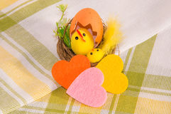 Decoração da Páscoa e três corações coloridos de feltro no napk do algodão Imagem de Stock