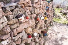 Decoração da parede de pedra do jardim com canecas do ferro, utensílios do ferro com flores Dia ensolarado fotografia de stock royalty free