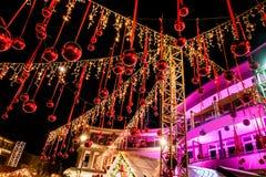 Decoração da rua do Natal: bolas vermelhas que penduram em cordas e em YE Foto de Stock