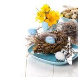 Decoração da tabela com o ninho dos ovos da páscoa na placa Fotografia de Stock