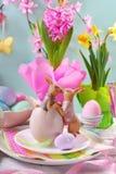 A decoração da tabela da Páscoa com coelhos e mola floresce foto de stock