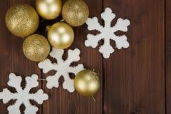 Decoração das bolas e dos flocos de neve do Natal do ouro no fundo de madeira Fotografia de Stock