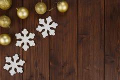 Decoração das bolas e dos flocos de neve do Natal do ouro no fundo de madeira Fotografia de Stock Royalty Free