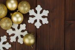 Decoração das bolas e dos flocos de neve do Natal do ouro no fundo de madeira Foto de Stock Royalty Free