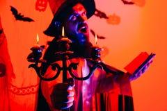 Decoração de Dia das Bruxas e conceito assustador O homem pronuncia um período, lê um livro mágico Música da noite 31 de outubro imagem de stock