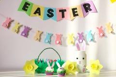 Decoração de Diy para a Páscoa Festões de papel, coelho do vaso, narcisos amarelos, coelhos dos ovos, cesta com ovos pintados imagem de stock