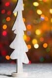 A decoração de madeira branca rústica da árvore que está na neve, com árvore de Natal ilumina-se Fotografia de Stock
