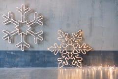 Decoração de madeira do Natal para as paredes Incandescer flocos de neve com festão ilumina-se no fundo concreto cinzento imagens de stock royalty free