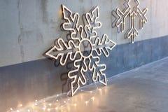 Decoração de madeira do Natal para as paredes Incandescer flocos de neve com festão ilumina-se no fundo concreto cinzento Backgro imagem de stock royalty free