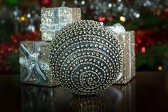 Decoração de prata do globo cercada por caixas de presente Imagens de Stock