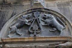 Decoração de um bas-relevo com os dois cães da pedra do espelho na fachada de uma casa medieval no centro histórico da cidade vel imagens de stock royalty free