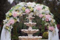 Decoração de uma cerimônia de casamento - um arco das flores na perspectiva da fonte Fotografia de Stock