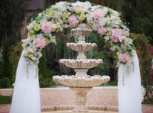Decoração de uma cerimônia de casamento - um arco das flores na perspectiva da fonte Imagens de Stock Royalty Free